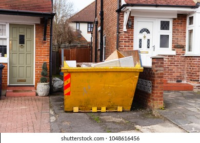 Yellow rubbish skip, on a driveway, next to house, England.