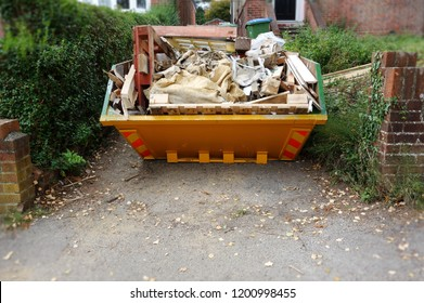 Yellow rubbish skip on driveway. Selective focus on full skip, with blurry house, green bush fence, brown brick wall. Empty space to add text in front of bin & footpath. House clearance moving concept