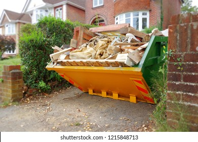 Yellow rubbish skip on driveway. Selective focus on full skip with space to add text in front of bin, brick wall, footpath, blurry green bush fence, houses in background. Renovate building concept.