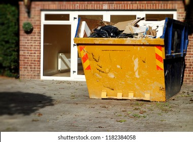 Yellow rubbish skip. Selective focus on full skip, right side of frame with space to add own text on blurry house, door, driveway & green bush fence in background. House clearance, moving concept.