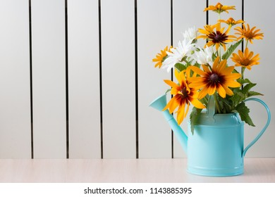 Yellow Rudbeckia, coneflowers, black-eyed-susans, flowers and other sumer flowers in a blue watering can