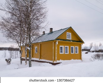 Yellow rural house with trees agains winter landscape