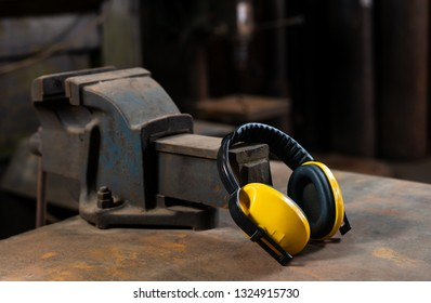 Yellow safety ear protection resting on an iron workshop vice bolted to a workbench