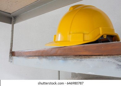 yellow safety engineer helmet on  wood background