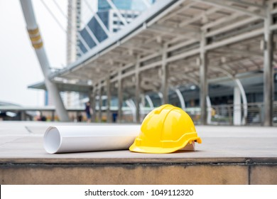 Yellow safety hard helmet with blueprint project on the city background