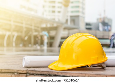 The yellow safety helmet and the blueprint at construction site with sunlight