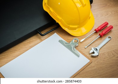 Yellow Safety Helmet Hat and clipboard,Drawing Paper Bags,  screwdriver,wrench on Wood background