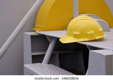 Yellow safety helmet on metal stairwell in cargo ship area, safety equipment in outdoor workplace concept