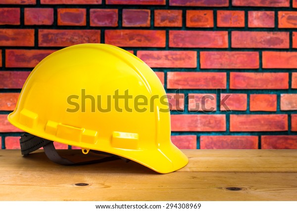 Yellow Safety Helmet on Wooden Floor with Brick Wall Background , color pop tone