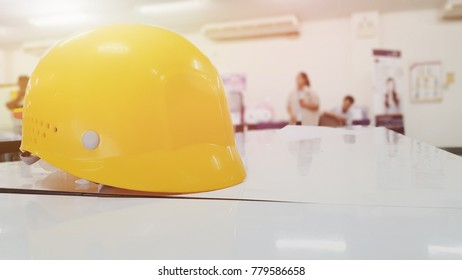 Yellow safety helmet placed on a white wooden desk on the background of the working man.