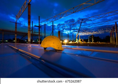 yellow safety helmet standing in front of oil refinery background