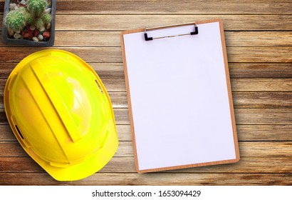Yellow safety helmet and white paper on Brown old wood background in office workplace.