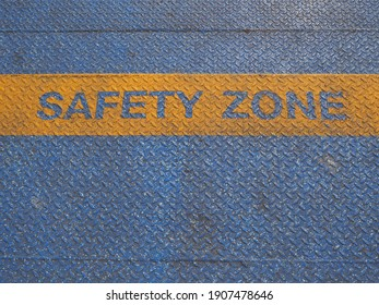 Yellow safety zone text on blue grunge, surface created using spray painting color. Sign for passenger on ferry pier.