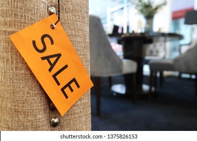 A yellow SALE tag on the sofa, with blurred furniture in the background, concept of store price discount marketing strategy to boost sales