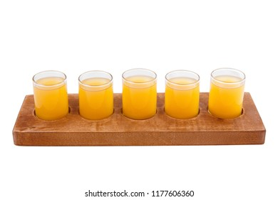 Yellow, same color opaque cocktails, a set of shots in one row, five servings on a wooden stand, substrate. Side view Isolated white background. Drink for the menu restaurant, bar, cafe