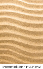 Yellow sand with waves on beach. Nature closeup in sunny day.