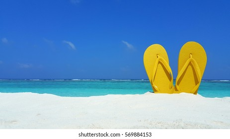 Yellow sandal flip flop on the white sand beach with blue sea and sky background in summer vacations copy space