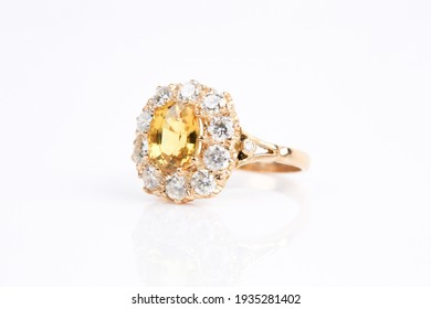 A yellow sapphire and diamond ring on a white background