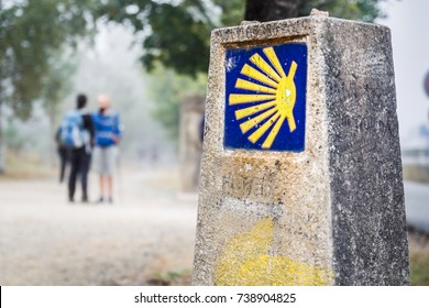 the yellow scallop shell signing the way to santiago de compostela on the st james pilgrimage route with two pilgrims chatting on the background