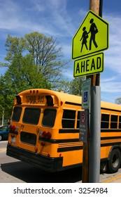 Yellow school bus rear parked near school sign