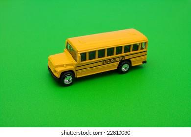 Yellow school bus sitting on green background, school bus