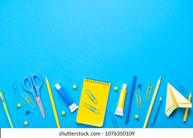 Yellow school supplies over the blue pastel background. Education, studing and back to school concept