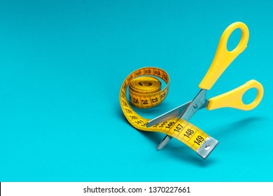 yellow scissors cutting measuring tape on the turquoise blue background. scissors cutting yellow measuring tape dieting concept. conceptual photo of levitating scissors and measuring tape copy space