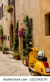 A Yellow Scooter parked near a Door full of Flowers in the streets of Pienza Village in Tuscany in a Sunny Summer Day