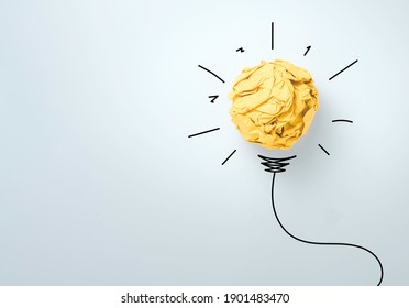 Yellow scrap paper ball with illustration painting for virtual lightbulb. It is creative thinking idea and innovation concept.