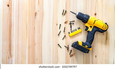 yellow screwdriver on a wooden table, screws, a set of bits.