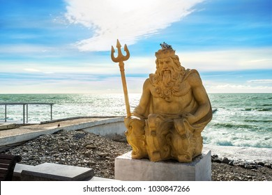 Yellow sculpture of Neptune with a trident on the Black Sea coast in sunny Sochi and a pigeon on his head