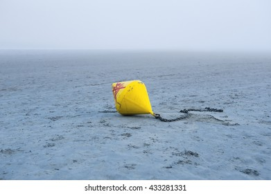 Yellow sea buoy thrown on the coast. In the shallows at low tide.
