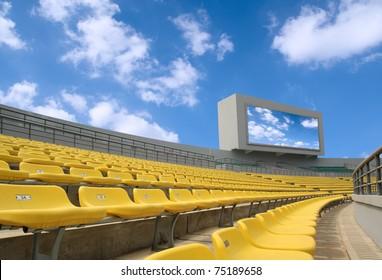 yellow seats and electronic billboard display at stadium