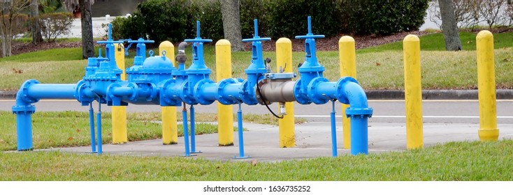 Yellow security bollards next to blue water main pipes