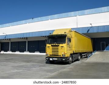 Yellow semi truck sitting at a loading dock
