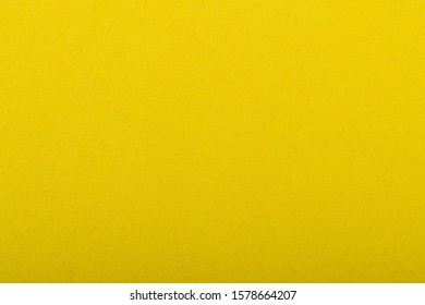 Yellow sheet of colored velvet paper. Bright color solid plain background. Horizontal orientation. Top view flat lay with copy space.