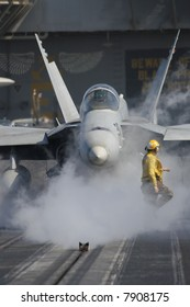 "A ""Yellow Shirt"" Aircraft Director in Front of an F/A-18F Super Hornet Aboard the Nuclear Aircraft Carrier, USS Enterprise"