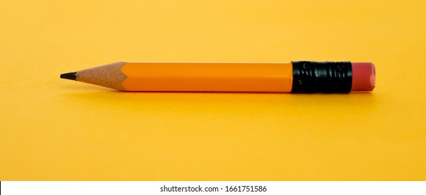 Yellow short pencil on yellow background.
