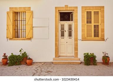 yellow shutters window and door on sidewalk in Cyprus