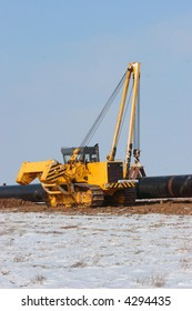 Yellow sideboom is carrying a big pipeline