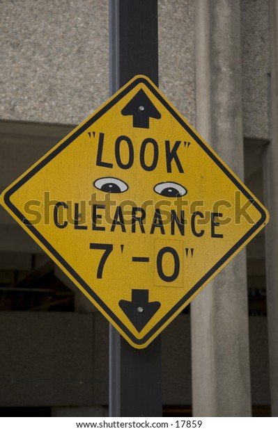 a yellow sign depicting: Look - Clearance 7'  sign has 2 eyes on it.