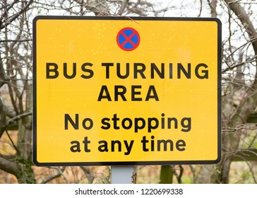 Yellow sign forbidding stopping in a bus turning area at any time.