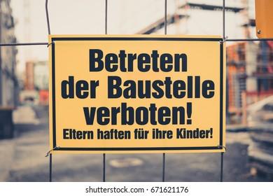 Yellow sign in german: Betreten der Baustelle verboten! Eltern haften fuer ihre Kinder! translation: entering the building site prohibited. Parents are responsible for their children
