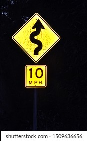 A Yellow Sign indicating 10 MPH and a curvy road with an arrow.