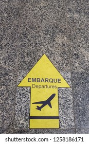 Yellow Sign on the floor Embarque in english means departures