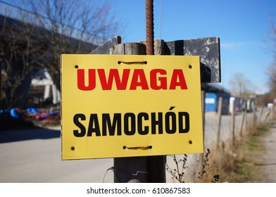 """Yellow sign in Polish text saying """"Watch out for cars"""" on a wooden pole by a road"""