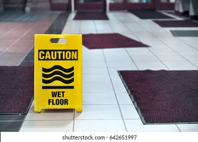 A yellow sign sitting on a tile floor with scattered rugs cautions about a wet floor