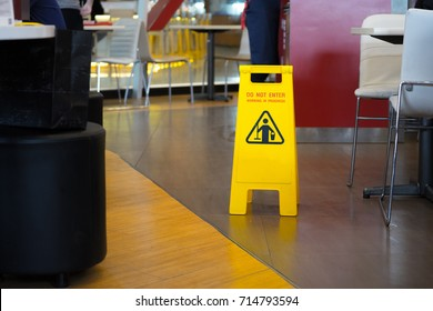 Yellow sign that alerts for wet floor in  the restaurant