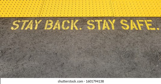 yellow sign at train station asking people to stay back, stay safe, on concrete floor