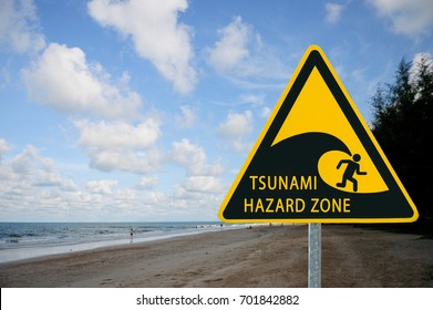 "Yellow sign ""Tsunami warning"" on Sea beach background"